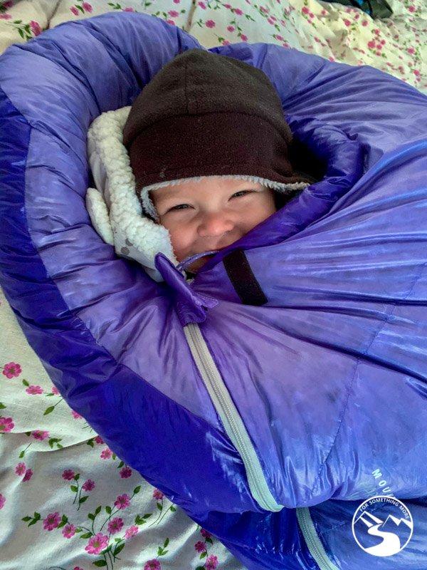 baby in sleeping bag while family trekking nepal