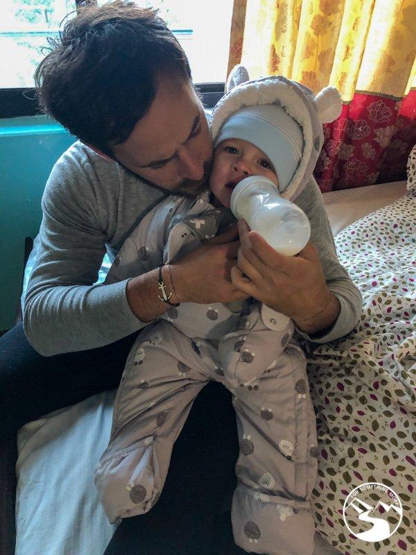 man feeing baby a bottle of milk in Ulleri Nepal
