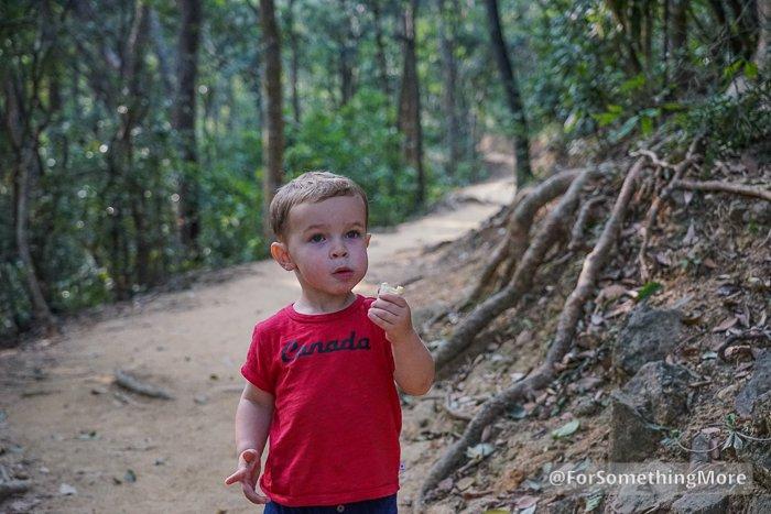 boy eating banana while hiking