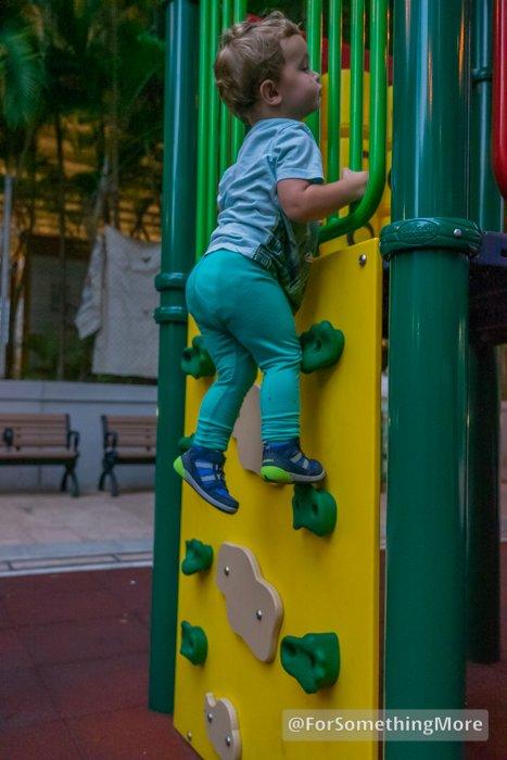 toddler climbing up rock wall at playground